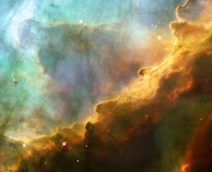 Like the fury of a raging sea, this anniversary image from the NASA/ESA Hubble Space Telescope shows a bubbly ocean of glowing hydrogen, oxygen, and sulphur gas in the extremely massive and luminous molecular nebula Messier 17. This Hubble photograph captures a small region within Messier 17 (M17), a hotbed of star formation. M17, also known as the Omega or Swan Nebula, is located about 5500 light-years away in the Sagittarius constellation. The release of this image commemorates the thirteenth anniversary of Hubble's launch on 24 April 1990. The wave-like patterns of gas have been sculpted and illuminated by a torrent of ultraviolet radiation from young, massive stars (which lie outside the picture to the upper left). The glow of these patterns highlights the 3D structure of the gases. The ultraviolet radiation is carving and heating the surfaces of cold hydrogen gas clouds. The warmed surfaces glow orange and red in this image. The intense heat and pressure cause some material to stream away from the surface, creating the glowing veil of even hotter green-coloured gas that masks background structures. The pressure on the tips of the waves may trigger new star formation within them. The image, roughly 3 light-years across, was taken on 29-30 May 1999, with Hubble's Wide Field Planetary Camera 2. The colours in the image represent various gases. Red represents sulphur; green, hydrogen; and blue, oxygen.