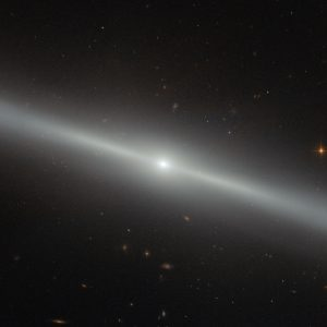 "This spectacular image was captured by the NASA/ESA Hubble Space Telescope's Advanced Camera for Surveys (ACS). The bright streak slicing across the frame is an edge-on view of galaxy NGC 4762, and a number of other distant galaxies can be seen scattered in the background. NGC 4762 lies about 58 million light-years away in the constellation of Virgo (The Virgin). It is part of the Virgo Cluster, hence its alternative designation of VCC 2095 for Virgo Cluster Catalogue entry. This catalogue is a listing of just over 2000 galaxies in the area of the Virgo Cluster. The Virgo Cluster is actually prominently situated, and lies at the centre of the larger Virgo supercluster, of which our galaxy group, the Local Group, is a member. Previously thought to be a barred spiral galaxy, NGC 4762 has since been found to be a lenticular galaxy, a kind of intermediate step between an elliptical and a spiral. The edge-on view that we have of this particular galaxy makes it difficult to determine its true shape, but astronomers have found the galaxy to consist of four main components — a central bulge, a bar, a thick disc and an outer ring. The galaxy's disc is asymmetric and warped, which could potentially be explained by NGC 4762 violently cannibalising a smaller galaxy in the past. The remains of this former companion may then have settled within NGC 4762's disc, redistributing the gas and stars and so changing the disc's morphology. NGC 4762 also contains a Liner-type Active Galactic Nucleus, a highly energetic central region. This nucleus is detectable due to its particular spectral line emission, which acts as a type of ""atomic fingerprint"", allowing astronomers to measure the composition of the region."