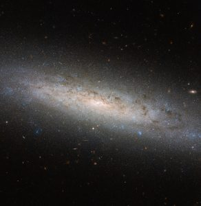This shining disc of a spiral galaxy sits approximately 25 million light-years away from Earth in the constellation of Sculptor. Named NGC 24, the galaxy was discovered by British astronomer William Herschel in 1785, and measures some 40 000 light-years across. This picture was taken using the NASA/ESA Hubble Space Telescope's Advanced Camera for Surveys, known as ACS for short. It shows NGC 24 in detail, highlighting the blue bursts (young stars), dark lanes (cosmic dust), and red bubbles (hydrogen gas) of material peppered throughout the galaxy's spiral arms. Numerous distant galaxies can also been seen hovering around NGC 24's perimeter. However, there may be more to this picture than first meets the eye. Astronomers suspect that spiral galaxies like NGC 24 and the Milky Way are surrounded by, and contained within, extended haloes of dark matter. Dark matter is a mysterious substance that cannot be seen; instead, it reveals itself via its gravitational interactions with surrounding material. Its existence was originally proposed to explain why the outer parts of galaxies, including our own, rotate unexpectedly fast, but it is thought to also play an essential role in a galaxy's formation and evolution. Most of NGC 24's mass — a whopping 80 % — is thought to be held within such a dark halo.