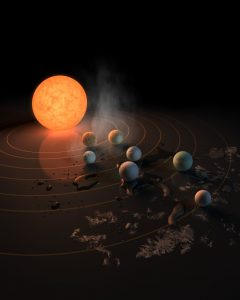 This artist's impression displays TRAPPIST-1 and its planets reflected in a surface. The potential for water on each of the worlds is also represented by the frost, water pools, and steam surrounding the scene. The image appears on the 22 February 2017 Nature cover.