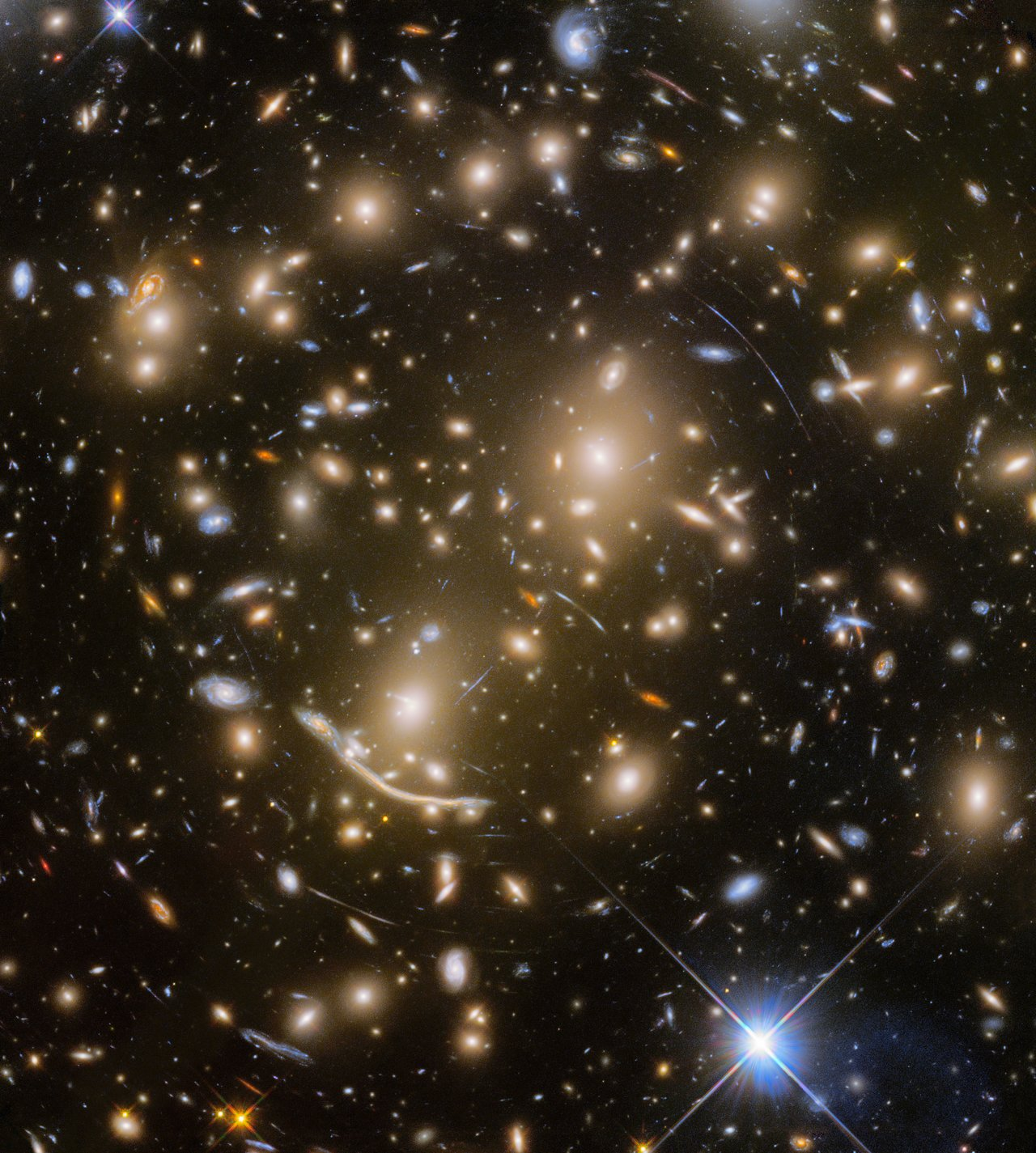 With the final observation of the distant galaxy cluster Abell 370 — some five billion light-years away — the Frontier Fields program came to an end. Abell 370 is one of the very first galaxy clusters in which astronomers observed the phenomenon of gravitational lensing, the warping of spacetime by the cluster's gravitational field that distorts the light from galaxies lying far behind it. This manifests as arcs and streaks in the picture, which are the stretched images of background galaxies.