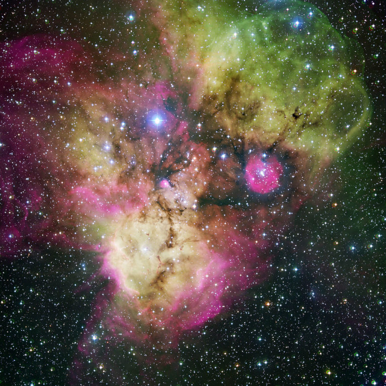 "Area surrounding the stellar cluster NGC 2467, located in the southern constellation of Puppis (""The Stern""). With an age of a few million years at most, it is a very active stellar nursery, where new stars are born continuously from large clouds of dust and gas. The image, looking like a colourful cosmic ghost or a gigantic celestial Mandrill, contains the open clusters Haffner 18 (centre) and Haffner 19 (middle right: it is located inside the smaller pink region — the lower eye of the Mandrill), as well as vast areas of ionised gas. The bright star at the centre of the largest pink region on the bottom of the image is HD 64315, a massive young star that is helping shaping the structure of the whole nebular region. This image is available as a mounted image in the ESOshop. #L"