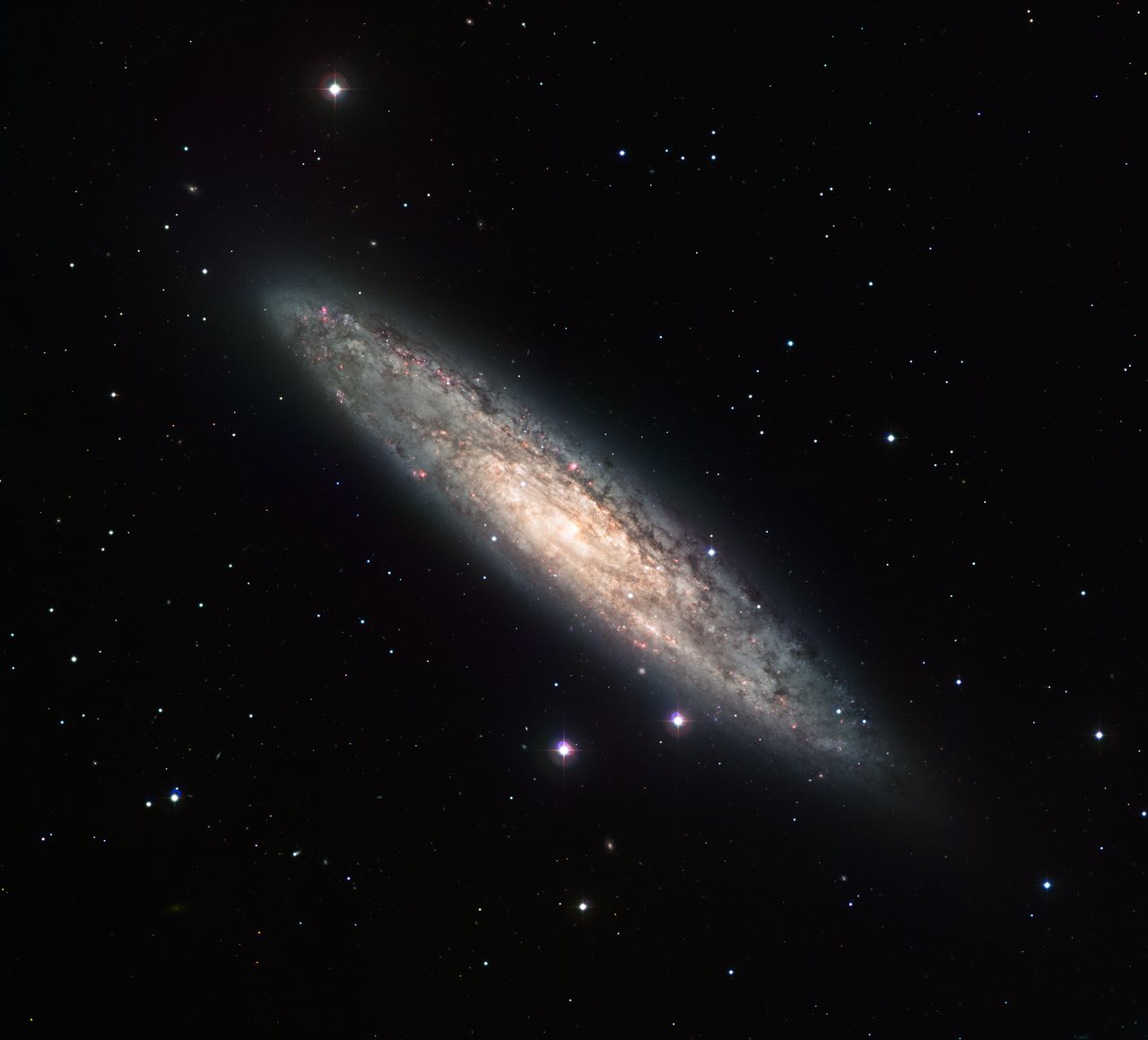 Measuring 70 000 light-years across and laying 13 million light-years away, the nearly edge-on spiral galaxy NGC 253 is revealed here in an image from the Wide Field Imager (WFI) on the MPG/ESO 2.2-metre telescope at the La Silla Observatory. The image is based on data obtained through four different filters (R, V, H-alpha and OIII). North is up and East to the left. The field of view is 30 arcminutes.
