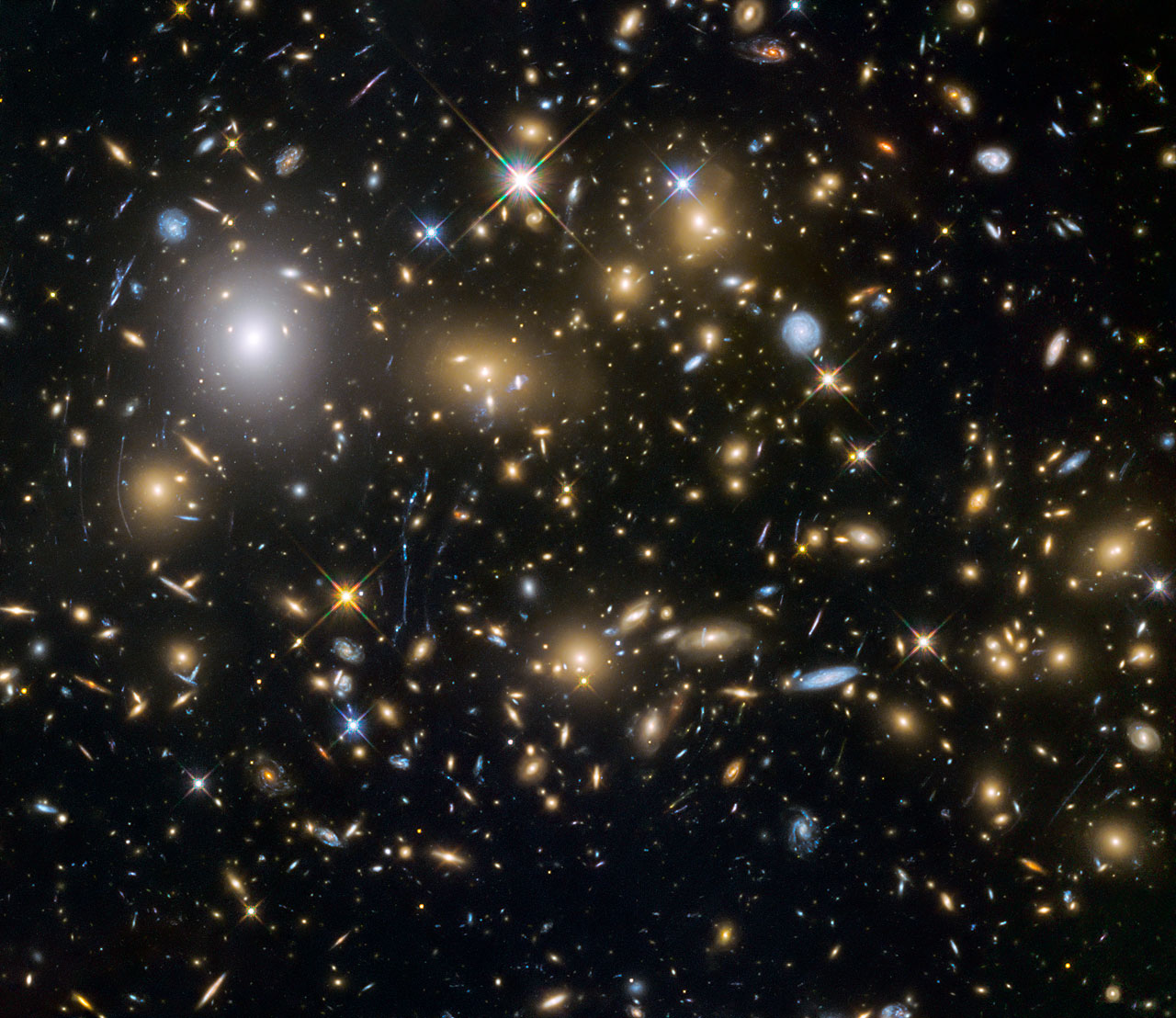 This image from the NASA/ESA Hubble Space Telescope shows the galaxy cluster MACSJ0717.5+3745. This is one of six being studied by the Hubble Frontier Fields programme, which together have produced the deepest images of gravitational lensing ever made. Due to the huge mass of the cluster it is bending the light of background objects, acting as a magnifying lens. It is one of the most massive galaxy clusters known, and it is also the largest known gravitational lens. Of all of the galaxy clusters known and measured, MACS J0717 lenses the largest area of the sky.